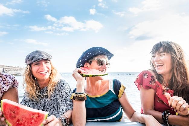 陽気な美しい若い女性は笑い、海と屋外の友情と赤いスイカを食べて一緒に楽しんでください