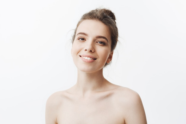 Cheerful beautiful young mother with long dark hair in bun hairdo being naked smiling bright fully , being happy about her motherhood. young family concept