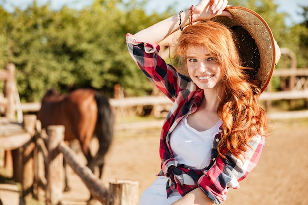Cheerful beautiful young woman cowgirl with her horse on ranch