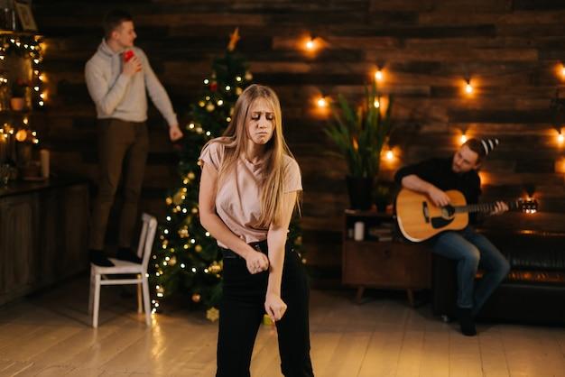 クリスマスツリーと花輪で飾られた壁を背景に新年会で踊る陽気な美しい若い女性。椅子で踊る男。男は椅子に座ってギターを弾きます。