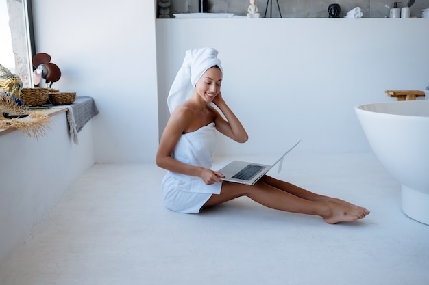 Cheerful beautiful young woman freelancer in white towel