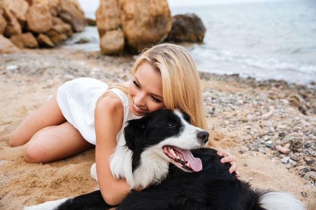 Веселая красивая молодая женщина обнимает собаку на пляже