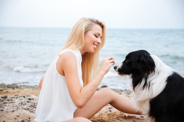 ビーチで彼女の犬を抱き締める陽気な美しい若い女性