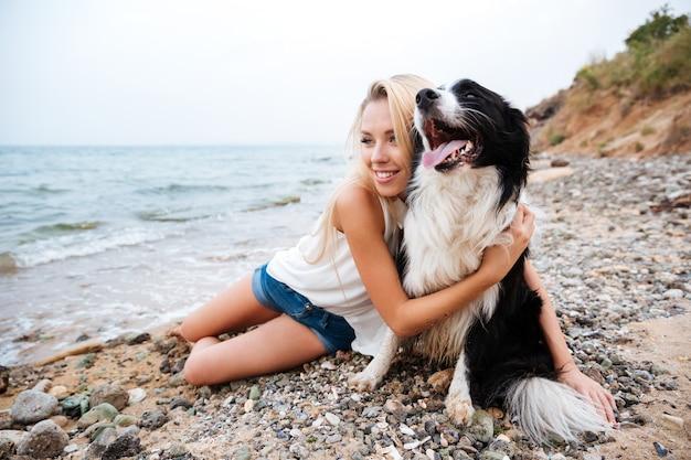 해변에서 개를 껴안고 있는 쾌활한 아름다운 젊은 여성