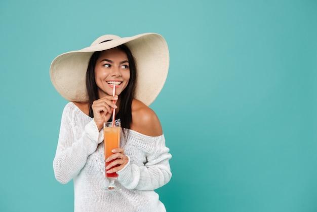 Веселая красивая молодая женщина в шляпе, пить коктейль с соломой