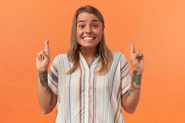 縞模様のシャツを着た陽気な美しい若い女性が微笑み、オレンジ色の壁を越えて指を組んでいる
