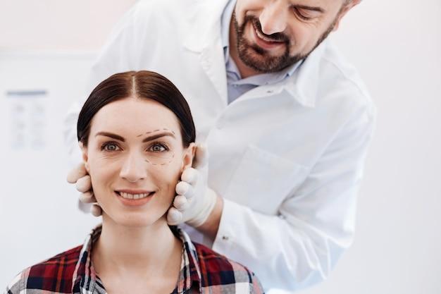 쾌활한 아름다운 젊은 여자가 그녀의 의사 앞에 앉아 얼굴 수술에 대해 종료되는 동안 웃고