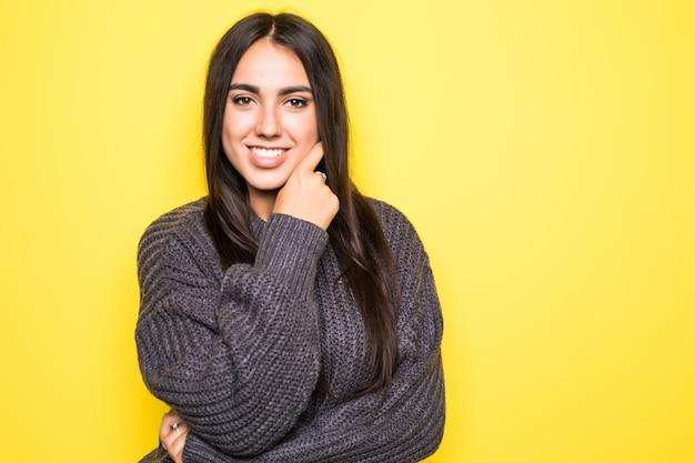 Cheerful beautiful young woman in sweater on yellow