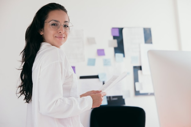 Cheerful beautiful young woman wear white shirt and round shaped glasses which holds papers looking at camera and smiling