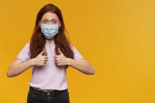 立って、黄色の壁に隔離された両手で親指を立てるジェスチャーを示す医療保護マスクを身に着けている陽気な美しい若い女性
