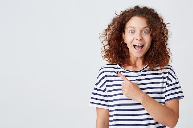곱슬 머리를 가진 밝고 아름다운 젊은 여성이 스트라이프 티셔츠를 입는다.