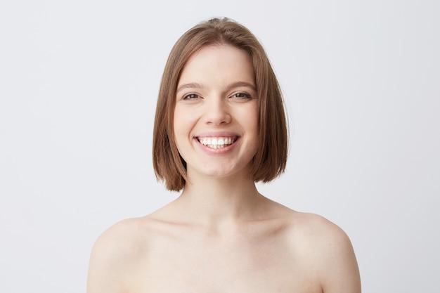 Bella giovane donna allegra con capelli scuri con pelle morbida e denti sani dopo l'applicazione della maschera