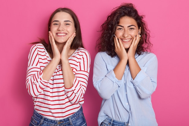 Cheerful beautiful young women with dark hair, looks laughing and touching her face by hand isolated over pink wall