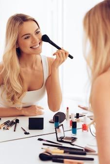 쾌활한 아름다움. 화장을 하고 화장대에 앉아 거울에 비친 자신의 모습을 바라보는 쾌활한 젊은 여성