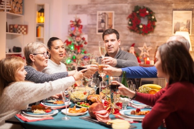 Cheerful big family clinking a glass of wine at christmas celebration.