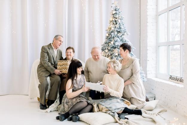 전나무 나무와 아늑한 방에 앉아있는 동안 크리스마스 선물을 여는 쾌활한 대가족