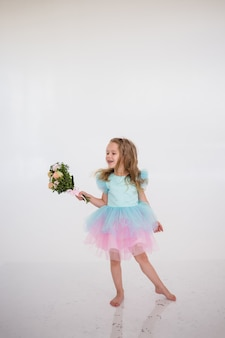 A cheerful birthday girl in a festive dress with a tutu skirt holds a bouquet of fresh flowers on a white background