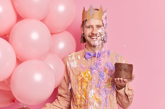 Cheerful birthday man smeared with cream holds chocolate cake gets congratulations on anniversary has festive mood enjoys free time on corporate party in office isolated over pink wall