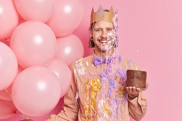 クリームを塗った陽気な誕生日の男はチョコレートケーキを保持します記念日にお祝いを取得ピンクの壁に隔離されたオフィスで企業のパーティーでお祭り気分を楽しんでいます