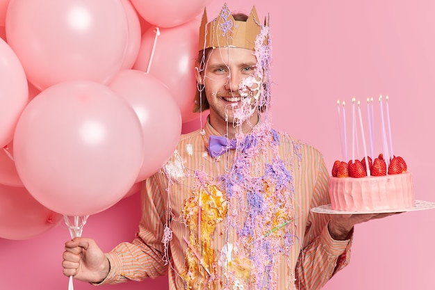 Cheerful birthday man with glad expression wears paper crown dirty festive clothes holds cake and balloons poses at party against pink wall celebrates anniversary or getting new position