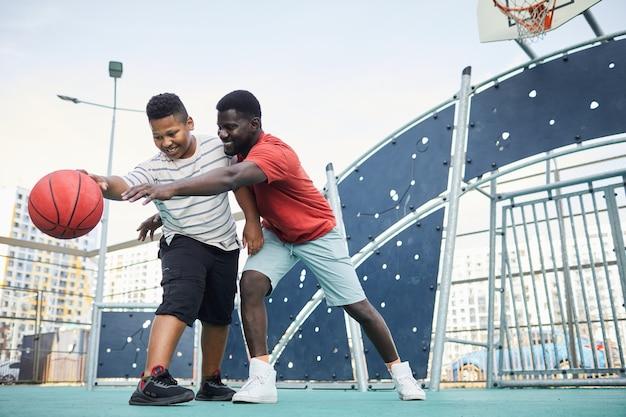 쾌활한 흑인 아버지가 도시 운동장에서 농구를 하는 동안 아들에게서 농구를 하려고 합니다.