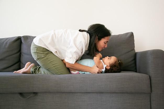회색 소파에 귀여운 아기 딸을 껴 안고 밝은 검은 머리 엄마. 측면보기. 부모와 어린 시절 개념