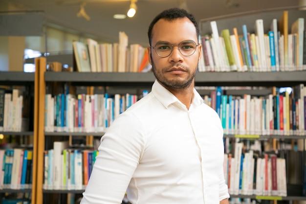 Веселый черный человек позирует в публичной библиотеке