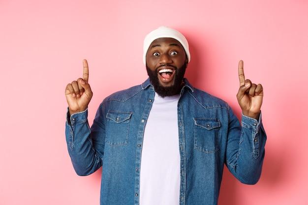 Allegro uomo di colore che mostra una fantastica offerta promozionale, puntando le dita in alto e sorridendo divertito, in piedi su sfondo rosa