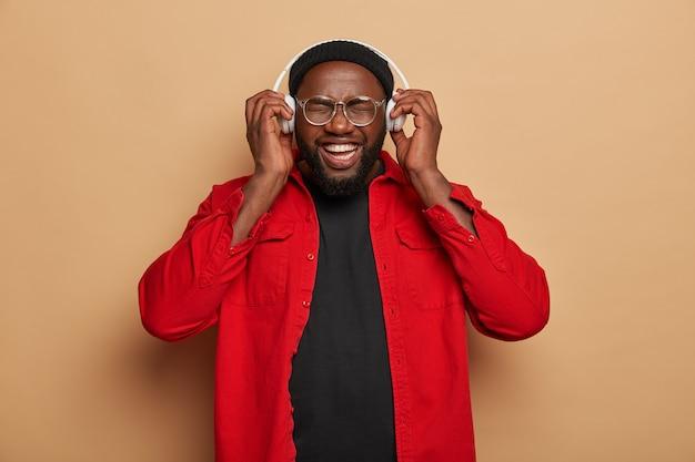 쾌활한 흑인 형태가 이루어지지 않은 남성 모델은 헤드셋에서 좋아하는 음악을 듣고 기뻐하며 웃음으로 얼굴을 가늘게 뜨고 있습니다.