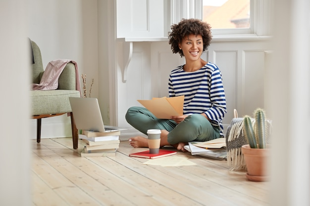 Cheerful black woman feels pleased, poses in lotus pose, reads financial report