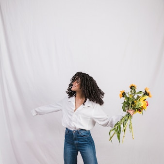 Cheerful black woman holding flowers bouquet