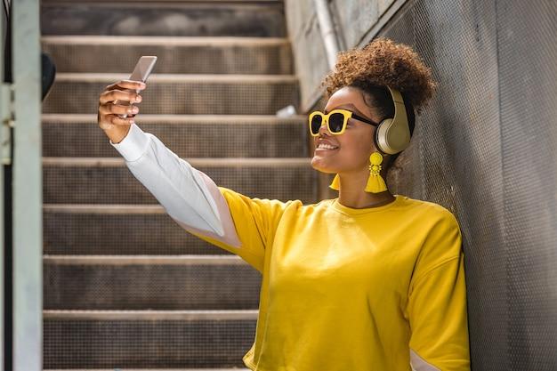 スマートフォンで自分撮りをしている流行の服装で陽気な黒人女性