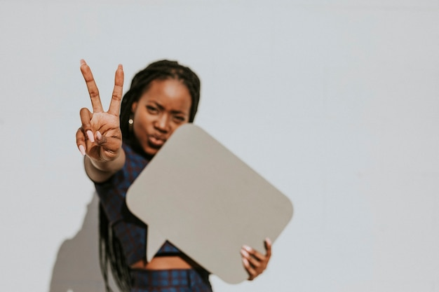 Cheerful black woman showing a v sign with a blank speech bubble