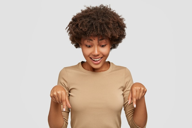Cheerful black young woman points down