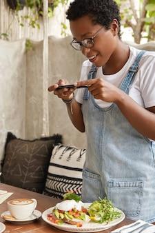 데님 옷을 입은 쾌활한 흑인 젊은이가 맛있는 이국적인 요리 사진을 만듭니다.