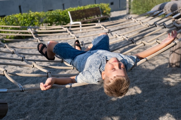 Cheerful blond boy smiling and lying on a rope swing in a public park.