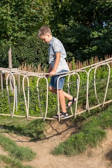 Cheerful blond boy walks on a rope bridge on a wooden playground in a public park.