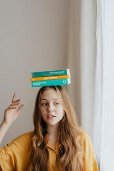 Веселая блондинка балансирует книги на голове
