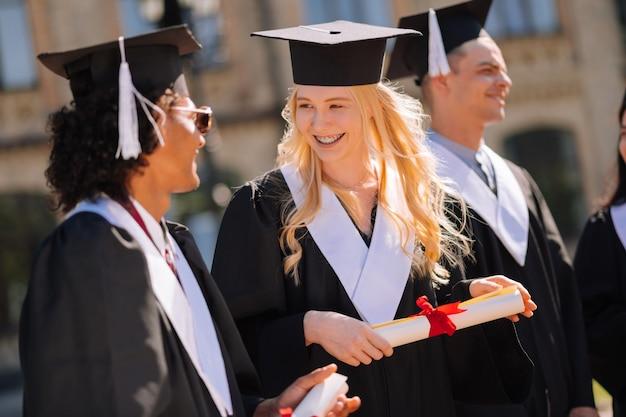 彼らの卒業の間に彼女のグループメートと話している彼女の転がされた卒業証書を持っている陽気なブロンドの女の子