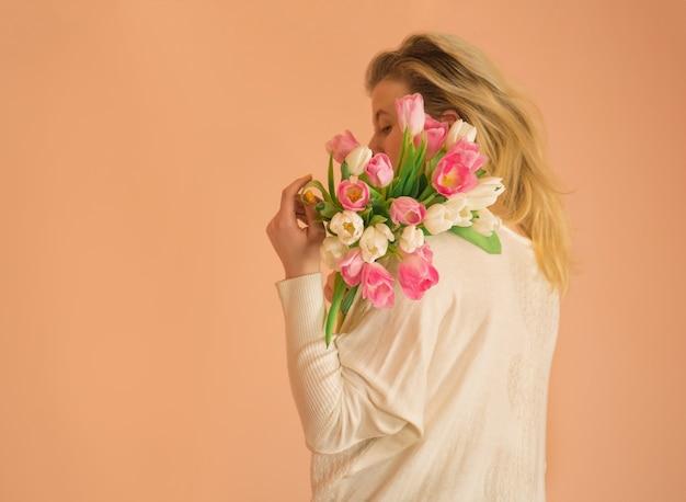 チューリップの花束を保持している陽気なブロンドの女の子。チューリップの花束を取っているカジュアルな服を着て幸せな少女の肖像画。