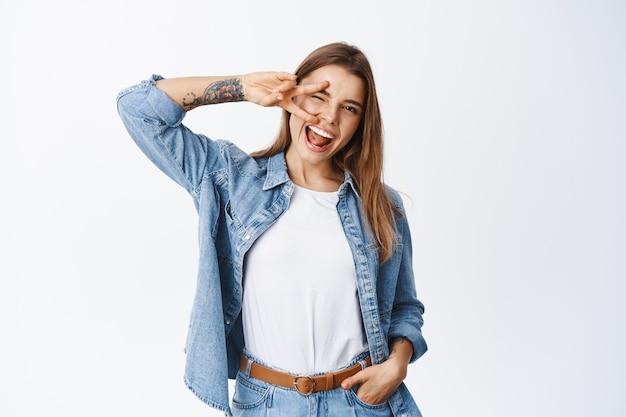 Allegra ragazza bionda che mostra segno di pace e strizza l'occhio davanti, divertendosi, sentendosi spensierata e ottimista, in piedi contro il muro bianco