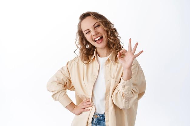 쾌활한 금발 소녀 윙크하고 괜찮은 표시를 보여주고, 멋진 제품을 칭찬하고, 추천하고, 좋은 선택을 칭찬하고, 흰 벽
