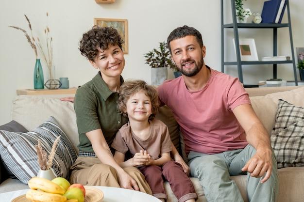 Веселый белокурый маленький мальчик в повседневной одежде сидит на диване между счастливыми родителями во время домашнего отдыха в гостиной