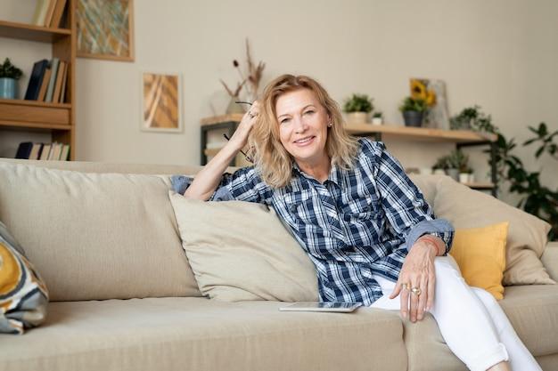 가정 환경에서 카메라 앞에 편안한 소파에 앉아 흰 청바지와 체크 무늬 셔츠에 밝은 금발 성숙한 여인