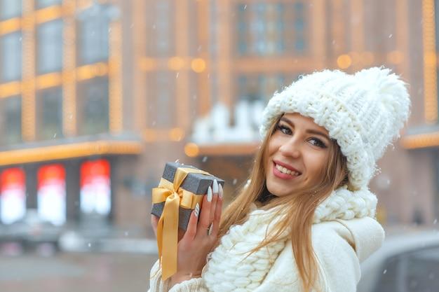 降雪時に通りでギフトボックスを保持している白いコートを着た陽気なブロンドの女性。テキスト用のスペース
