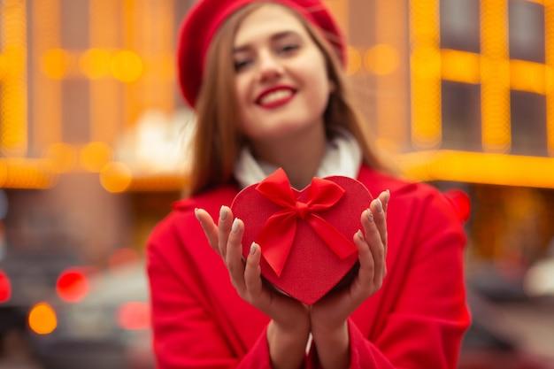 陽気な金髪の女性は、ボケライトの背景にハート型のギフトボックスを保持している赤いベレー帽とコートを着ています。テキスト用のスペース