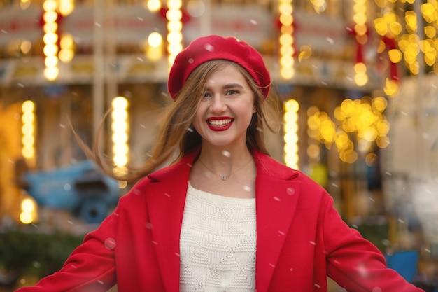 陽気な金髪の女性は、ライトでカルーセルの近くでポーズをとって赤いベレー帽と冬のコートを着ています。テキスト用のスペース
