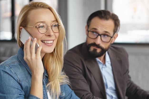 Веселая блондинка привлекательная женщина делает деловой звонок