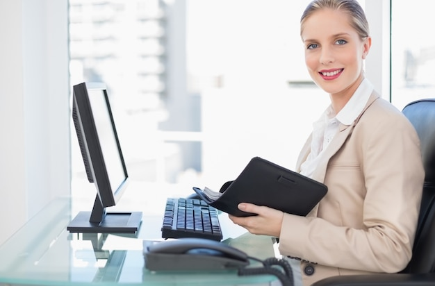 Cheerful blonde businesswoman holding datebook