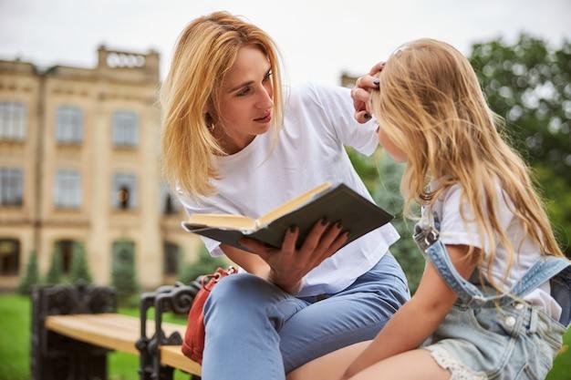 야외에서 시간을 보내는 동안 그녀의 작은 딸에게 동화를 읽고 쾌활한 금발 여성